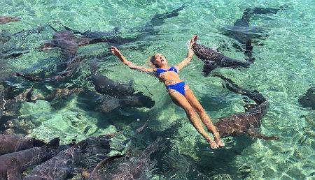 Modelo mordida, tirada hacia abajo mientras posa con tiburones durante sesión de fotos de Instagram